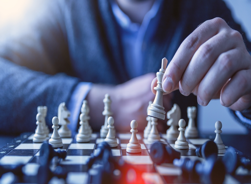 Man plays chess   chessboard with partly overthrown figures